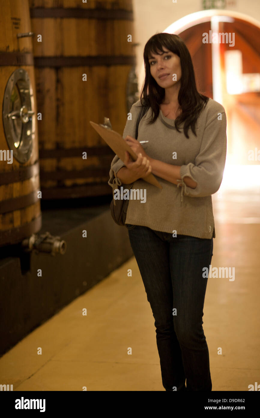 Woman standing next to barrels of wine - Stock Image