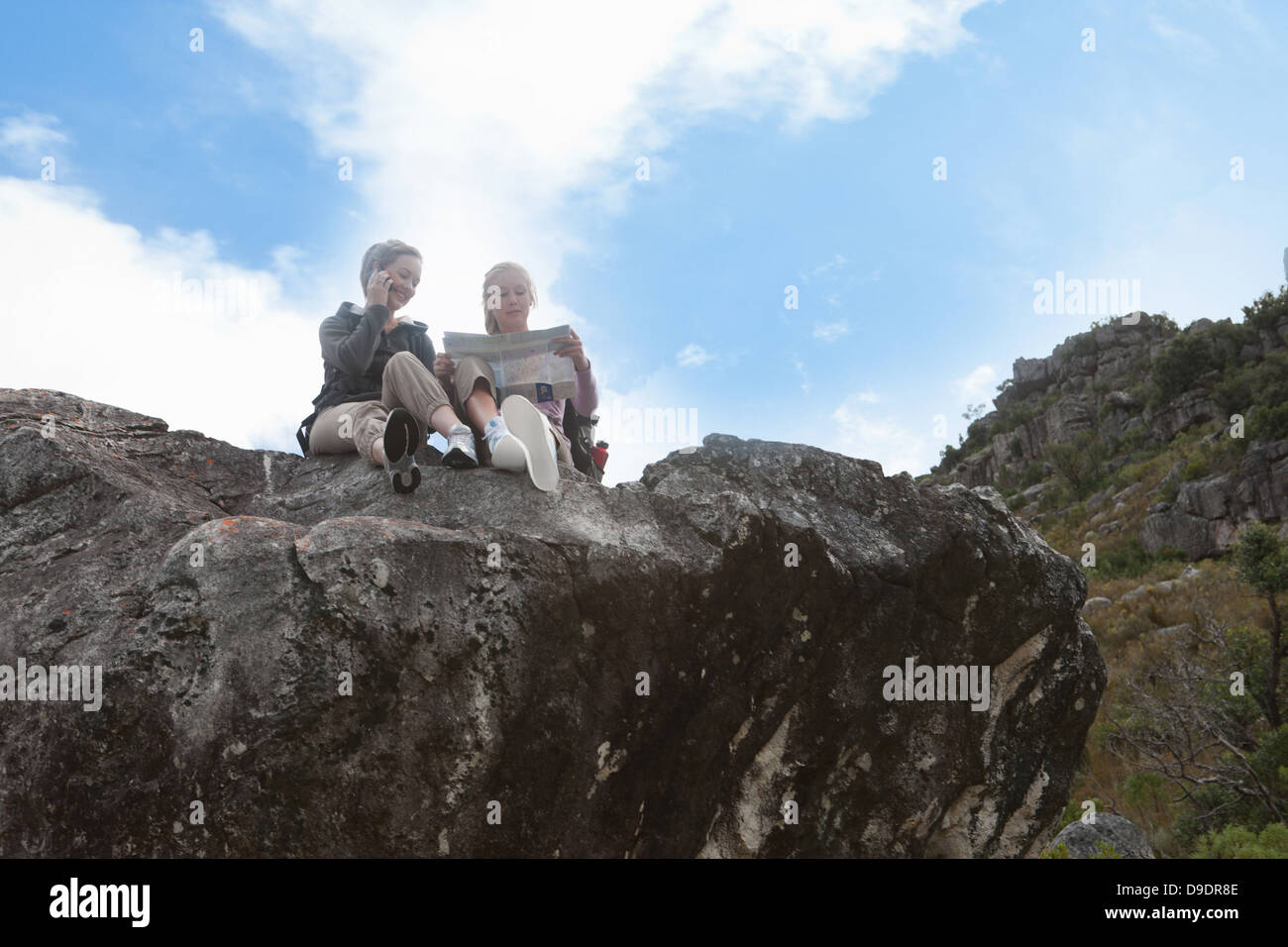 Two girl hikers reading map on top of rock formation - Stock Image