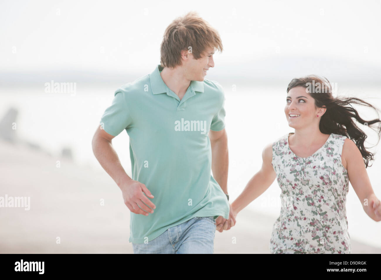 Young couple looking at each other whilst running - Stock Image