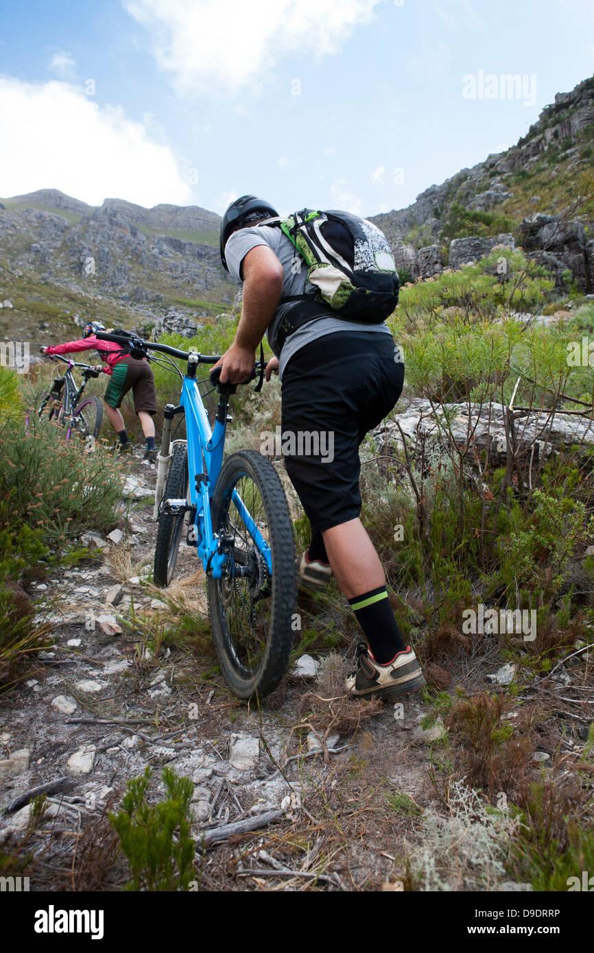 Young couple pushing mountain bikes up mountain path - Stock Image
