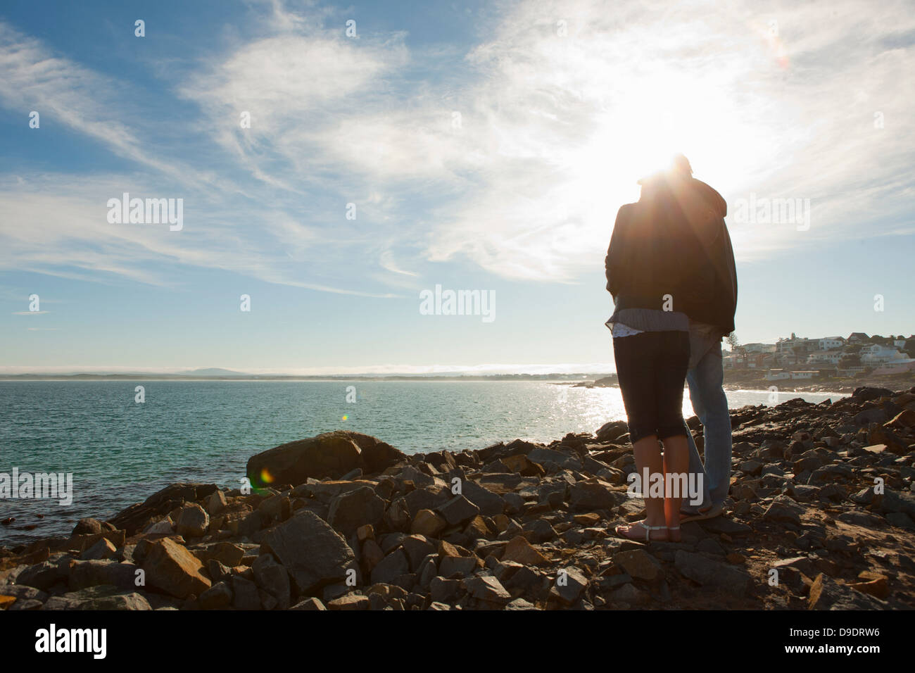 Young couple looking out to sea and horizon - Stock Image