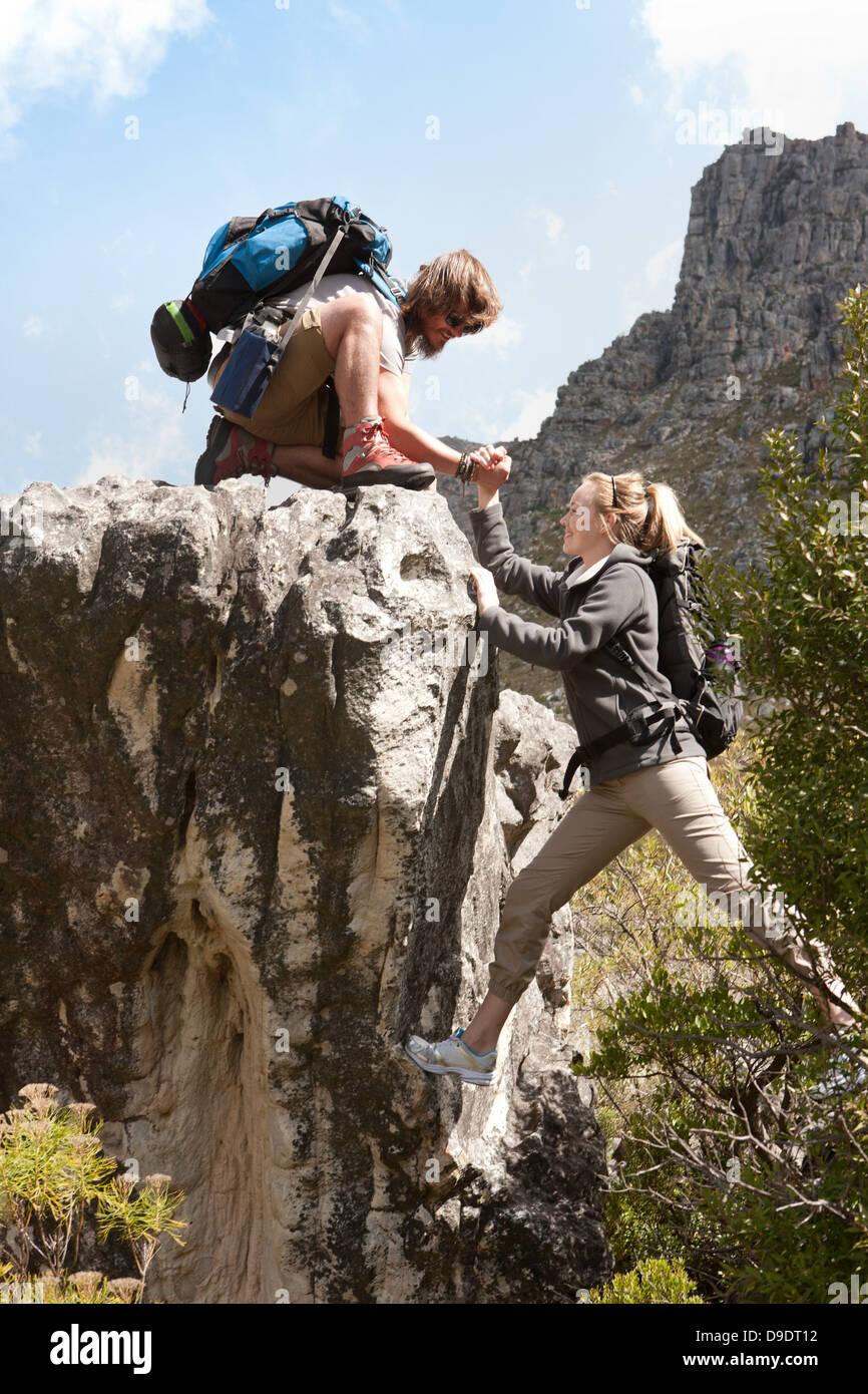 Hiking couple climbing rock formation Stock Photo