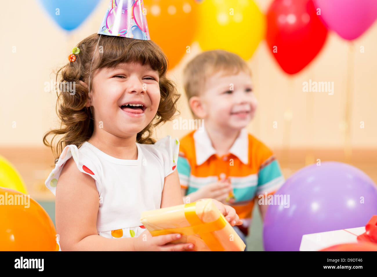 happy child girl with colorful balloons and gift - Stock Image
