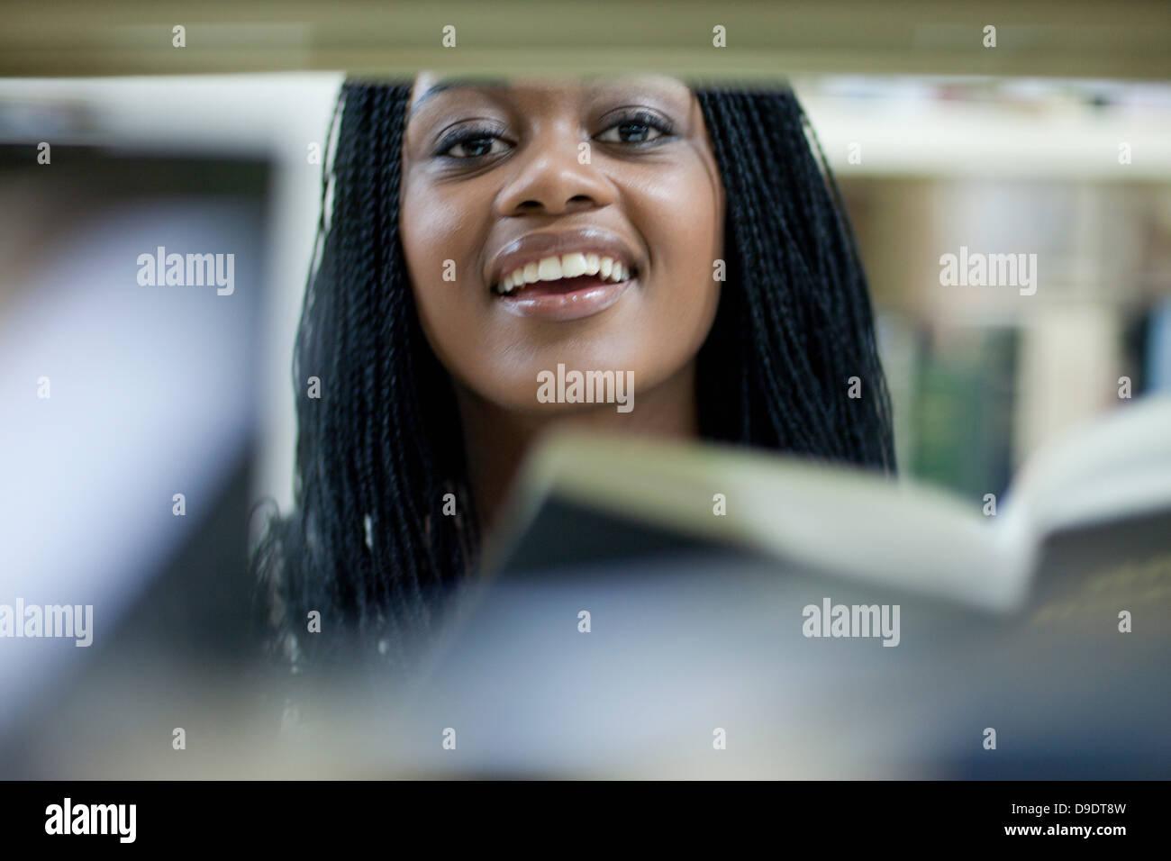 Female student peering between books - Stock Image