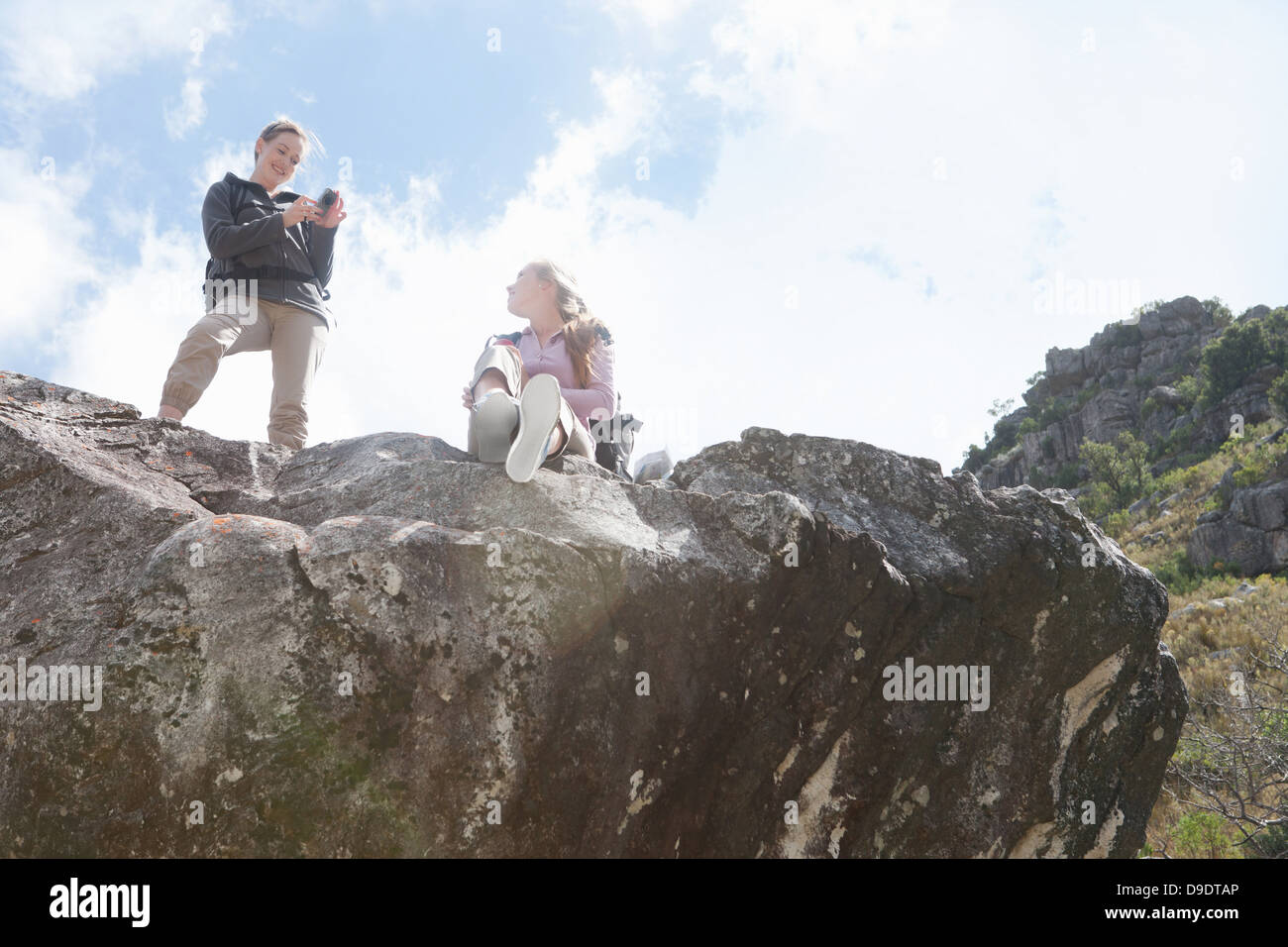 Two girl hikers photographing on top of rock formation - Stock Image