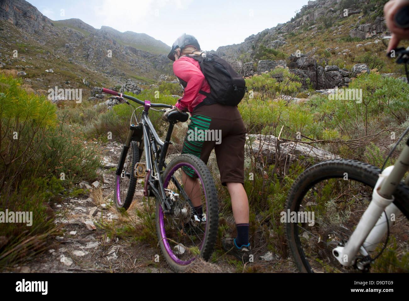 Young woman pushing mountain bike up mountain path Stock Photo