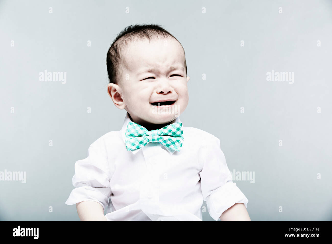Portrait of baby boy wearing shirt and bow tie, crying - Stock Image