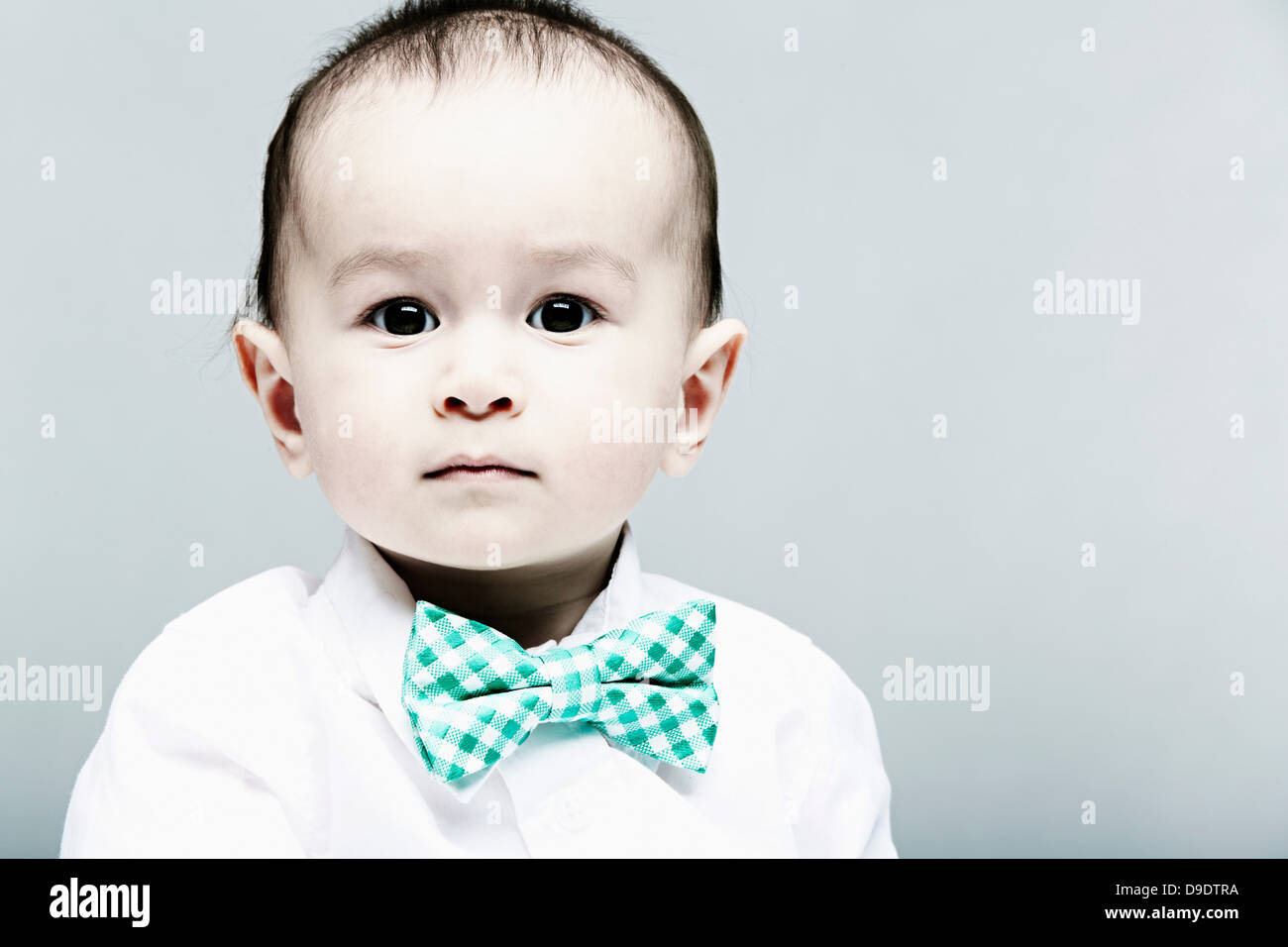 Portrait of baby boy wearing shirt and bow tie - Stock Image
