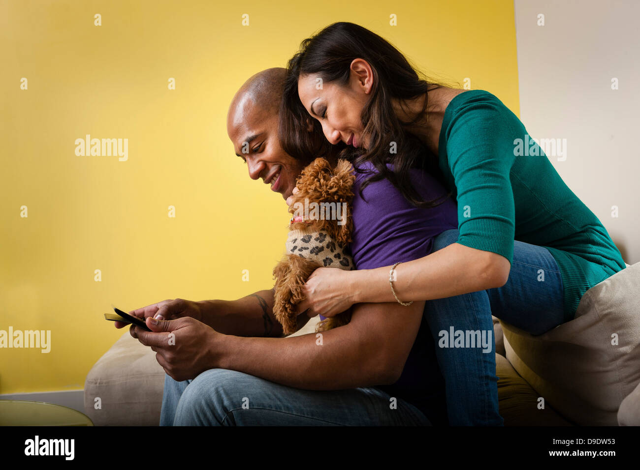 Mid adult couple sitting on sofa with dog and smartphone - Stock Image