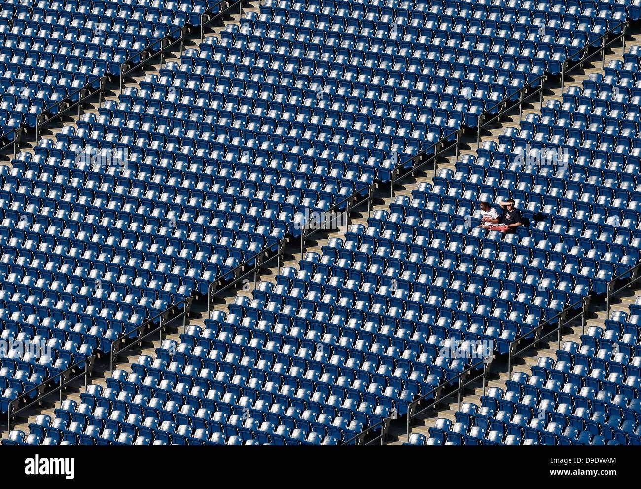 two people sitting in empty stadium - Stock Image