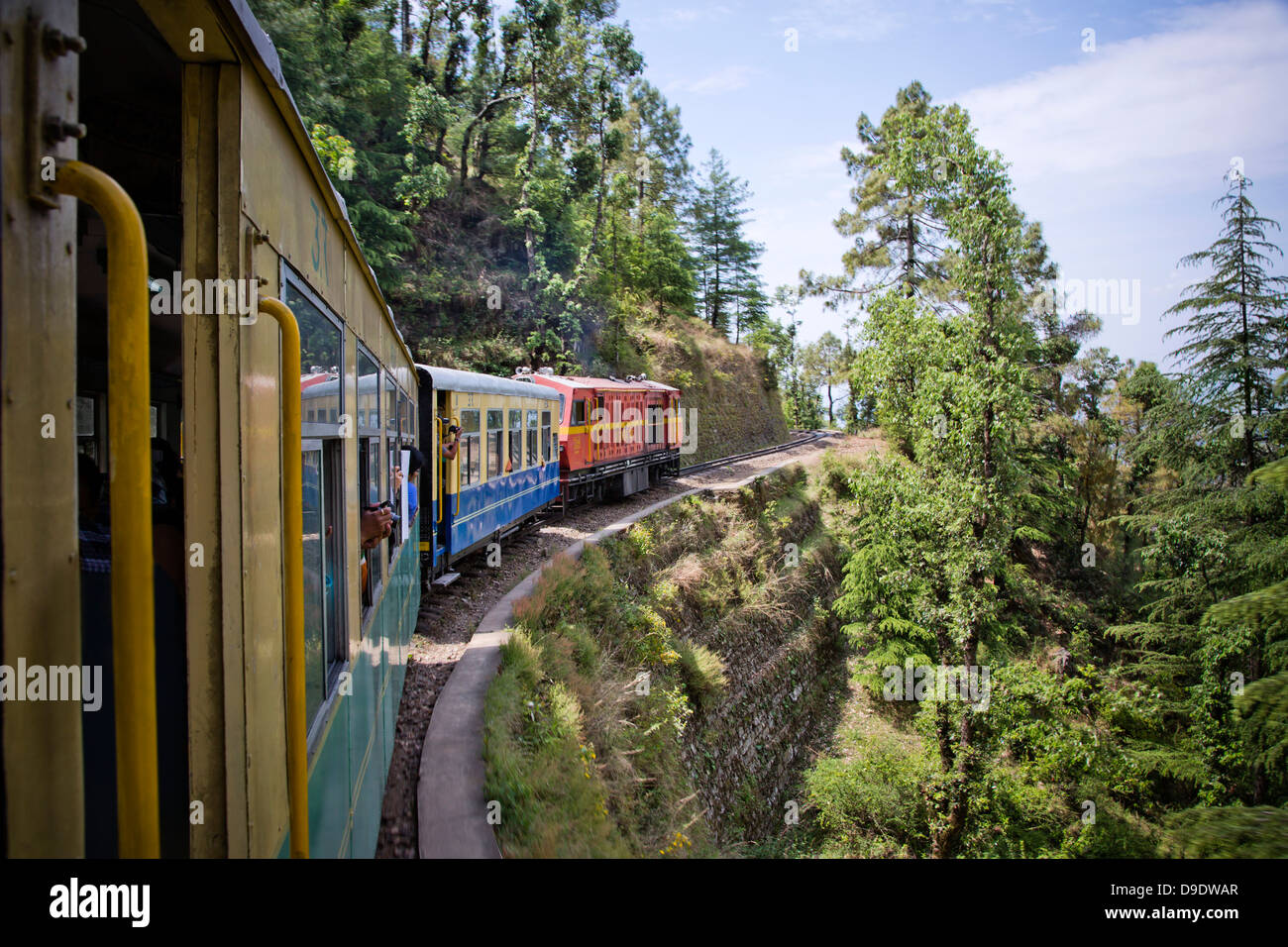 Train moving on railroad track in valley, Shimla, Himachal Pradesh, India - Stock Image
