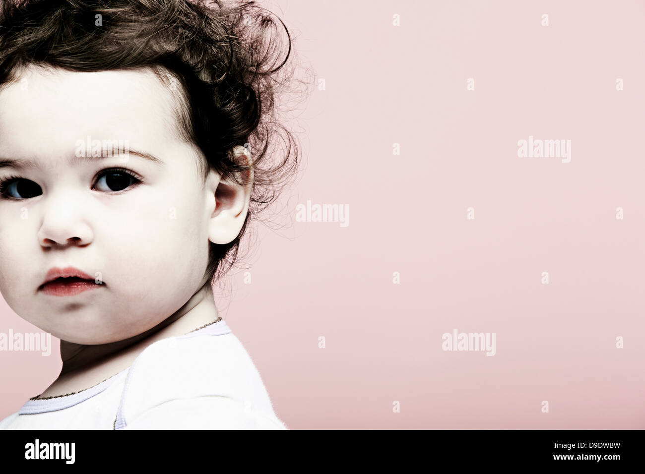 Portrait of baby girl against pink background - Stock Image