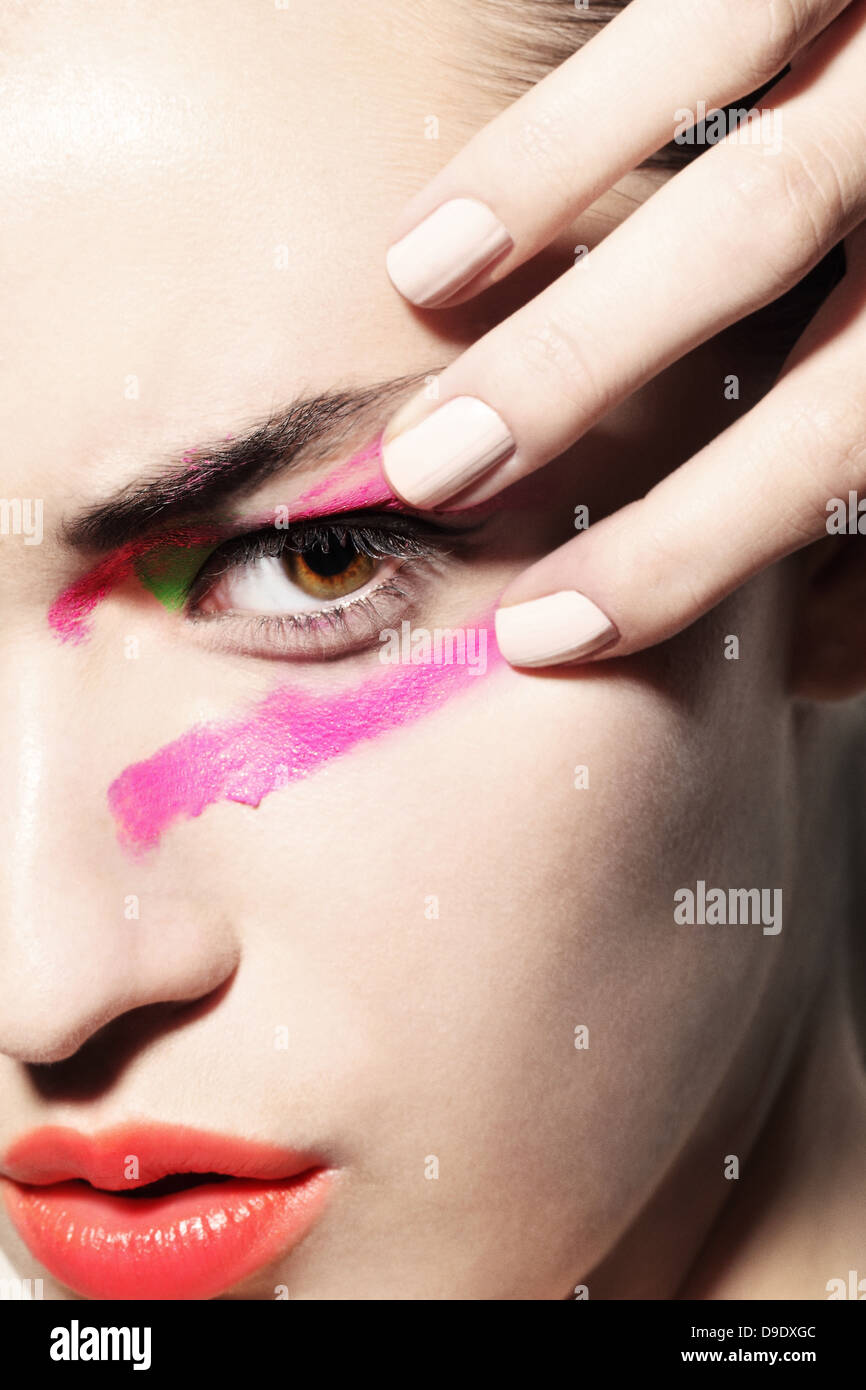 Woman smudging bright coloured make up on face Stock Photo