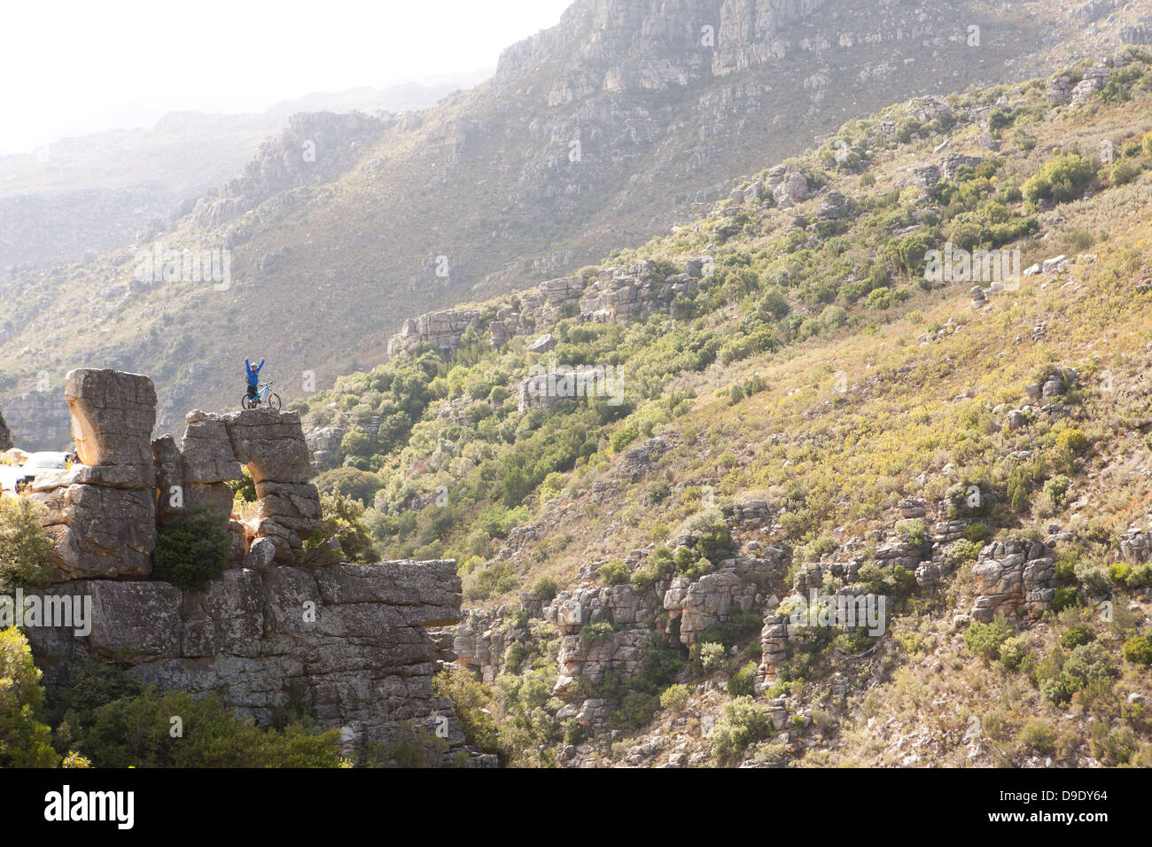 Distant view of young man with mountain bike on rock - Stock Image