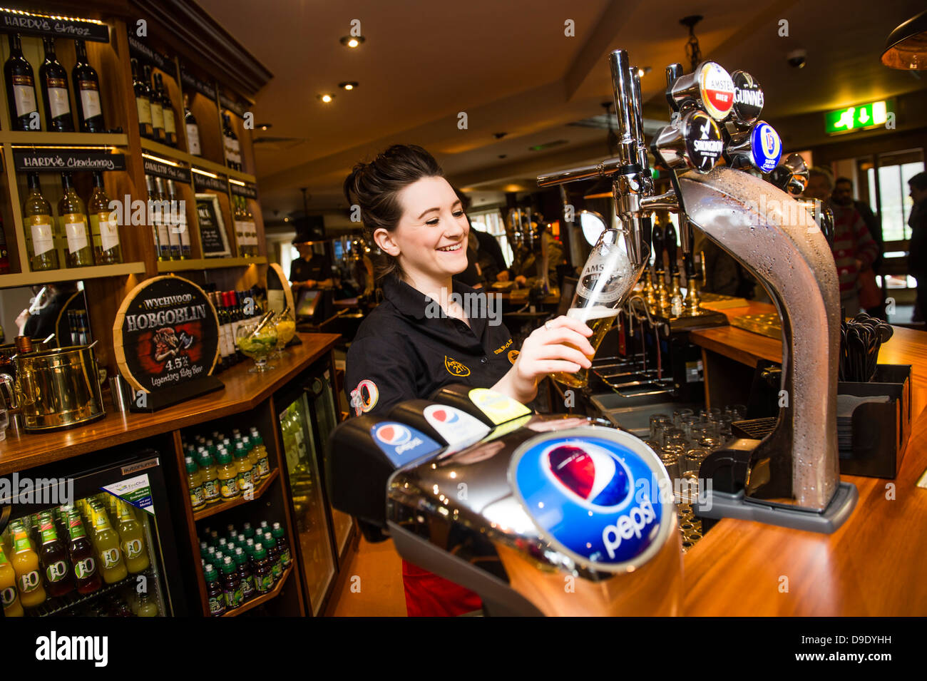 A barmaid working pouring a pint of lager beer in a pub bar UK - Stock Image