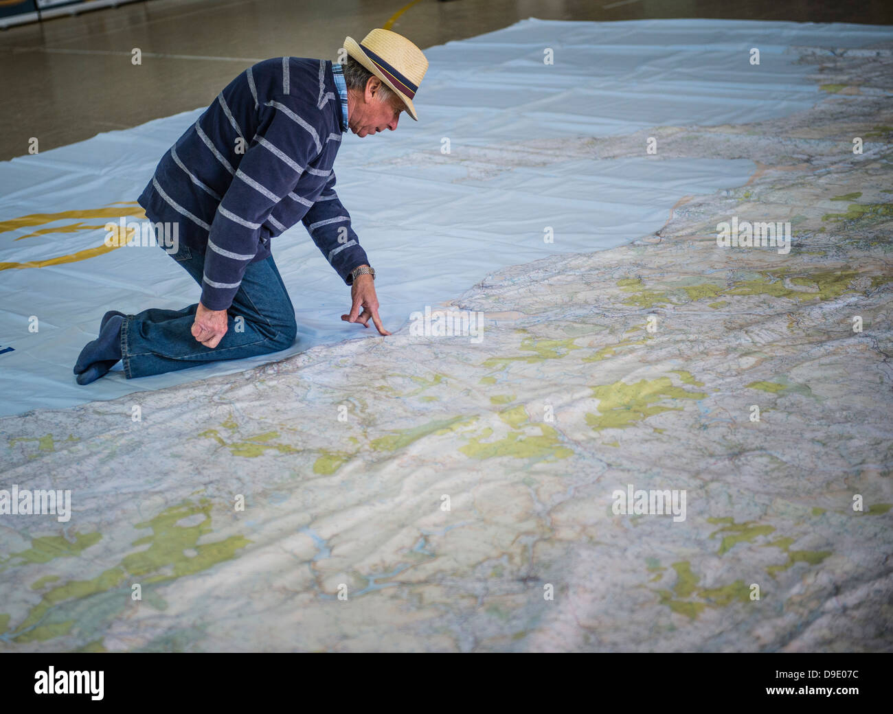 A man looking and crawling on an enormous large Ordnance Survey map of Wales - Stock Image