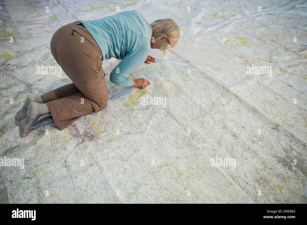 A woman looking and crawling on an enormous large Ordnance Survey map of Wales - Stock Image