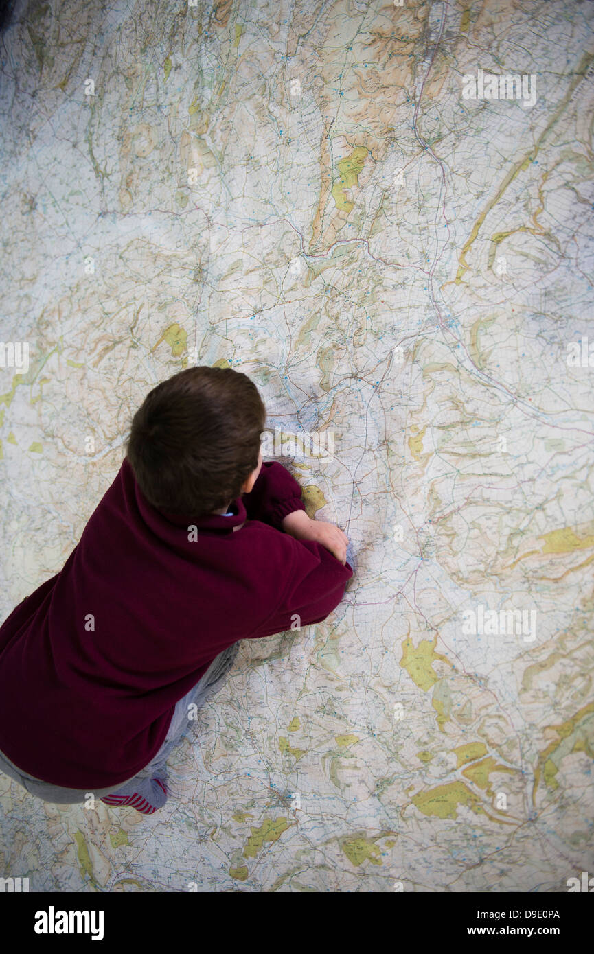 A child looking and crawling on an enormous large Ordnance Survey map of Wales - Stock Image