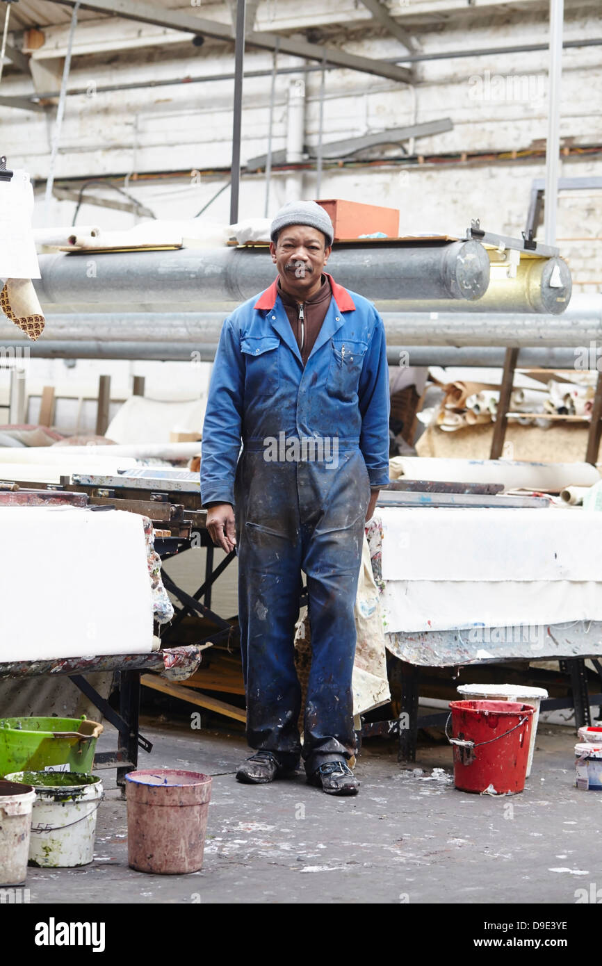 Portrait of man wearing boiler suit in screen printing factory - Stock Image