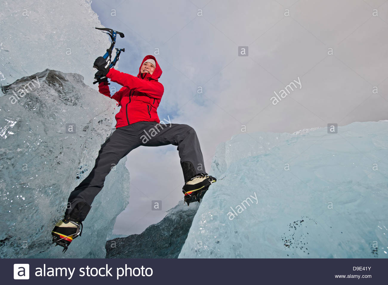 Mature woman climbing on iceberg, Jokulsa Loni, Iceland - Stock Image