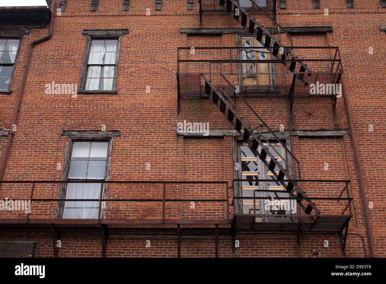 OLD BRICK BUILDING BLACK METAL FIRE ESCAPES STEPS STAIRS WINDOWS RAILING - Stock Image