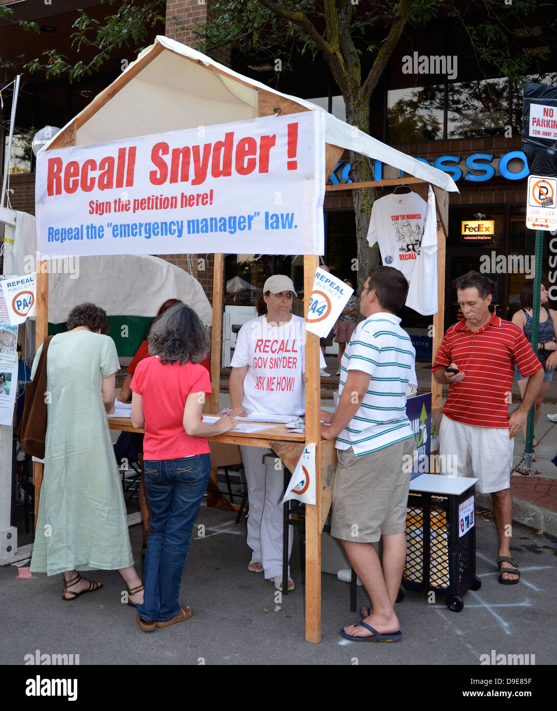 Supporters of an effort to recall Michigan Governor Rick Snyder staff a booth to gather petition signatures - Stock Image