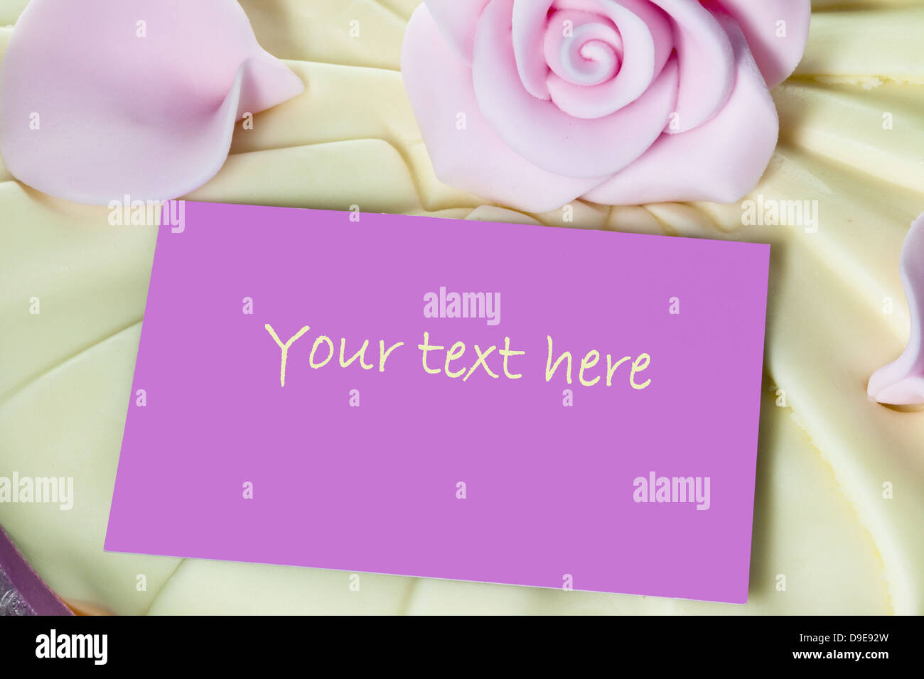 Pink note card close up on top of an iced cake. - Stock Image