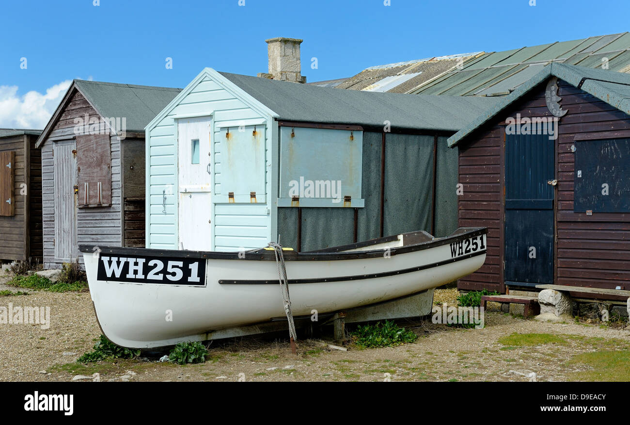 Rowing boat on dry land next to some beach huts Portland Bill Dorset England UK - Stock Image