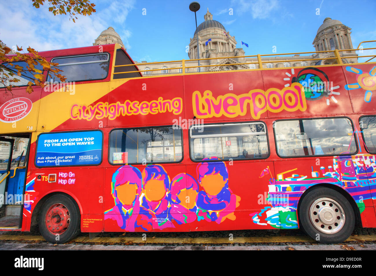 Sightseeing bus with colourful pictures of Beatles in Liverpool city centre. - Stock Image