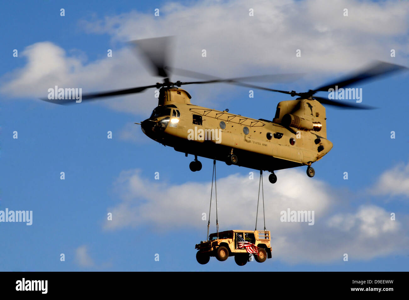 A U.S. Army CH-47 Chinook helicopter transports a Humvee. - Stock Image