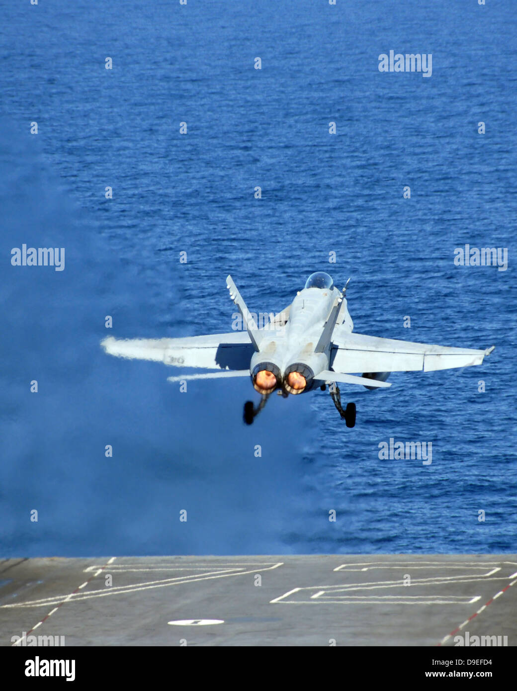 An F/A-18C Hornet launches from the USS Abraham Lincoln. - Stock Image