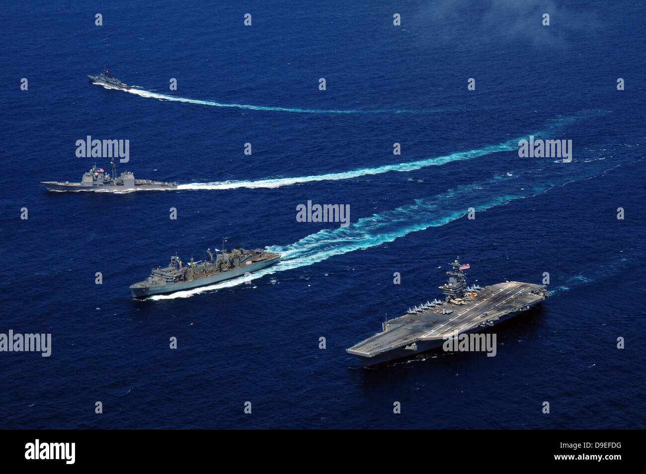 The USS Bunker Hill, the USNS Rainier, and the BAP Carvajal break away from the aircraft carrier USS Carl Vinson - Stock Image