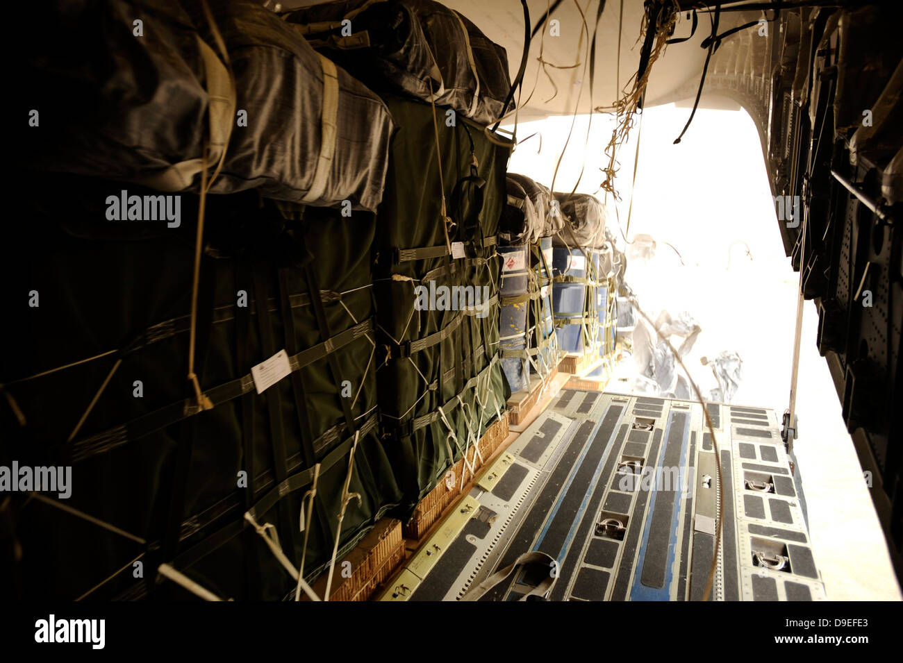Container delivery system bundles drop out of a C-17 Globemaster III over a drop zone in Afghanistan. - Stock Image