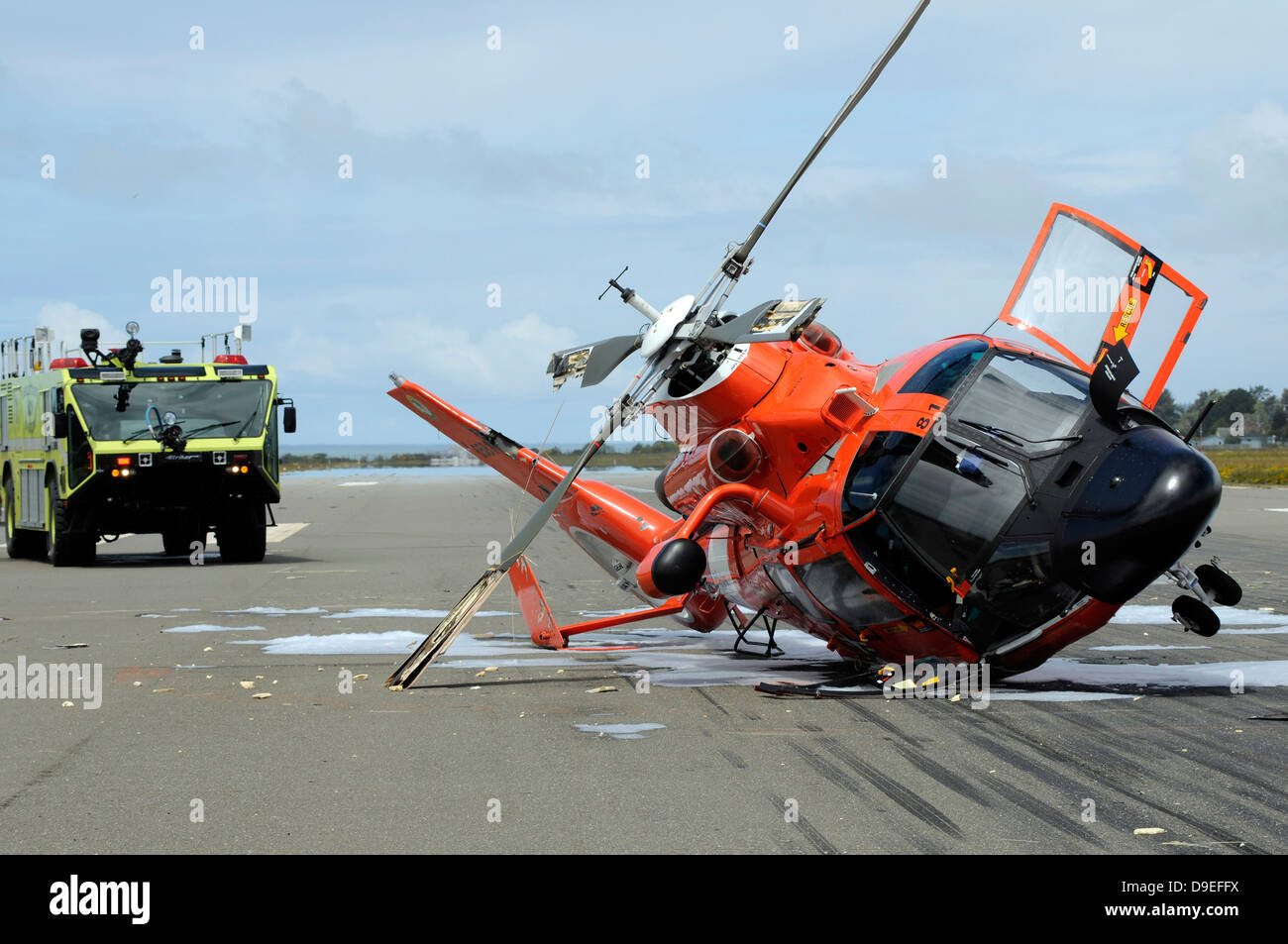 A U S  Coast Guard MH-65 Dolphin helicopter lays on its side