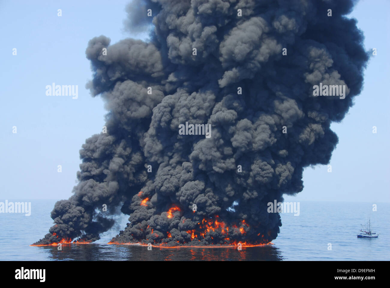 Dark clouds of smoke and fire emerge as oil burns during a controlled fire in the Gulf of Mexico. - Stock Image