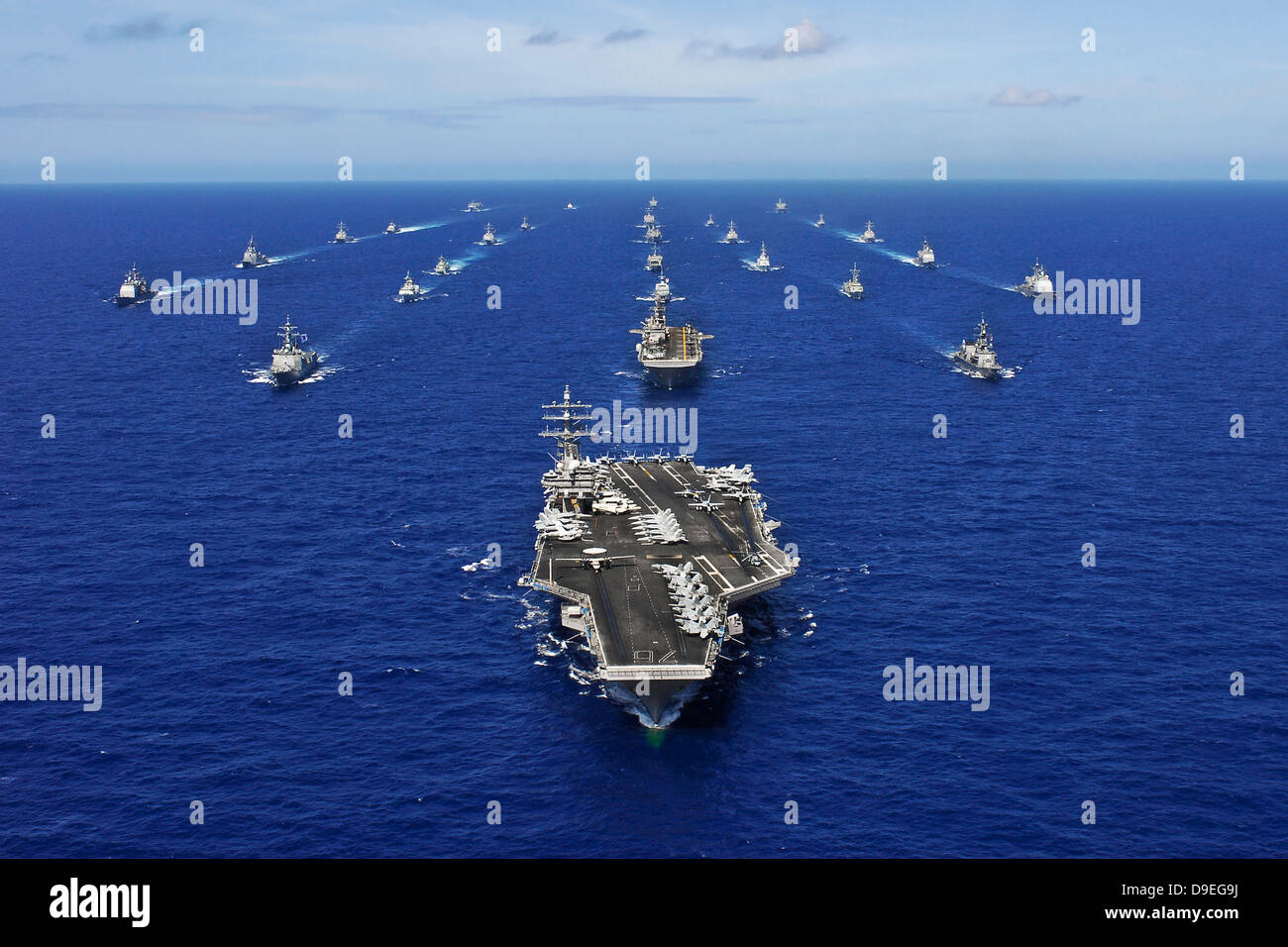 Aircraft carrier USS Ronald Reagan transits the Pacific Ocean with a fleet of ships. Stock Photo