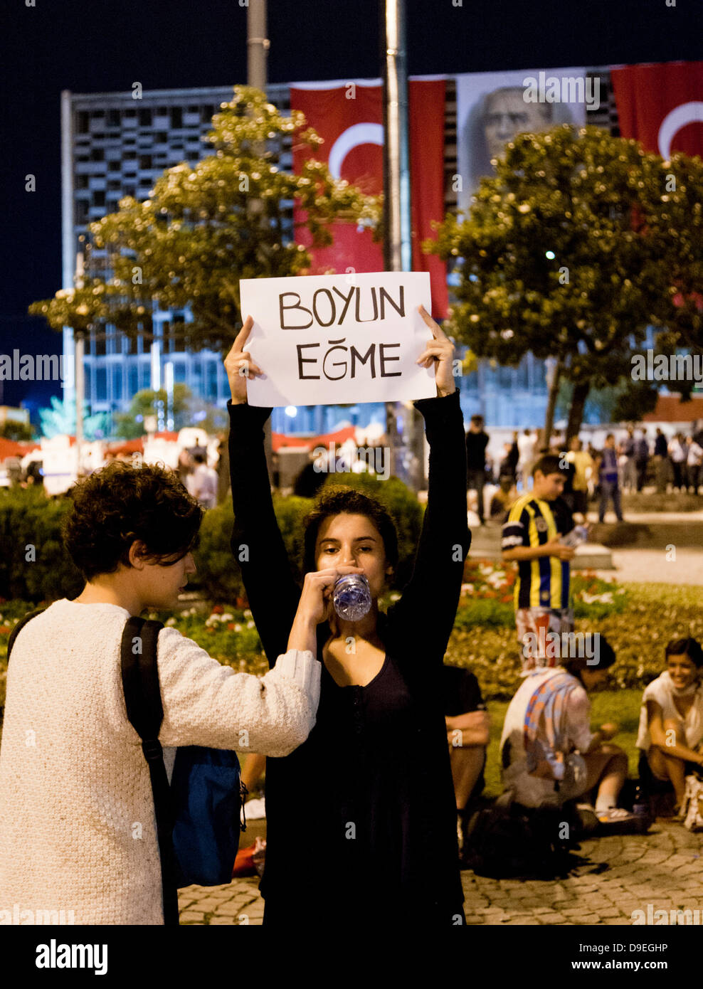 A woman demonstrating in Taksim Square as a silent protest against the government in Istanbul holding a sign that - Stock Image