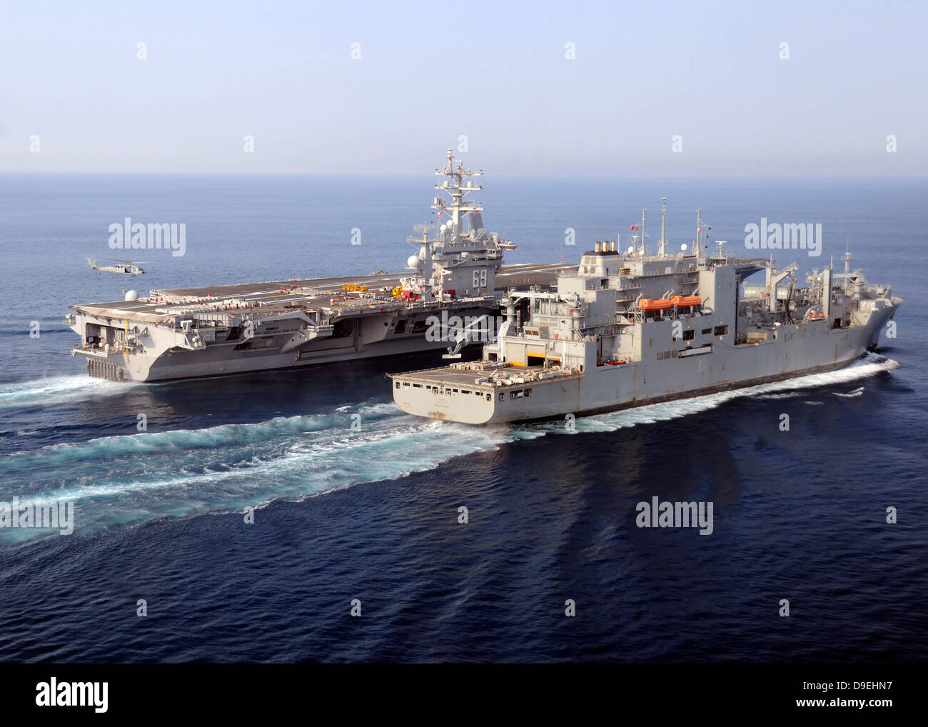 The Military Sealift Command dry cargo and ammunition ships conduct a vertical replenishment. - Stock Image