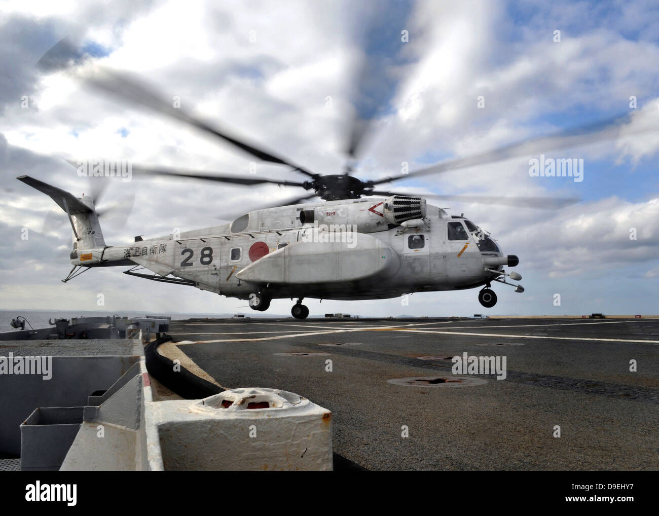 A Japanese Maritime Self-Defense Force MH-53 Sea Stallion lands on the flight deck of USS Denver. - Stock Image