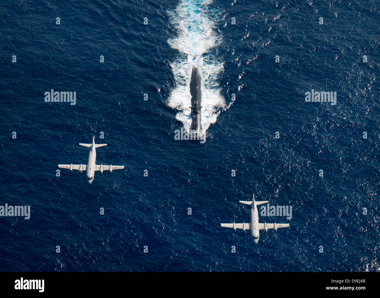 Two P-3 Orion maritime surveillance aircraft fly over attack submarine USS Houston. - Stock Image