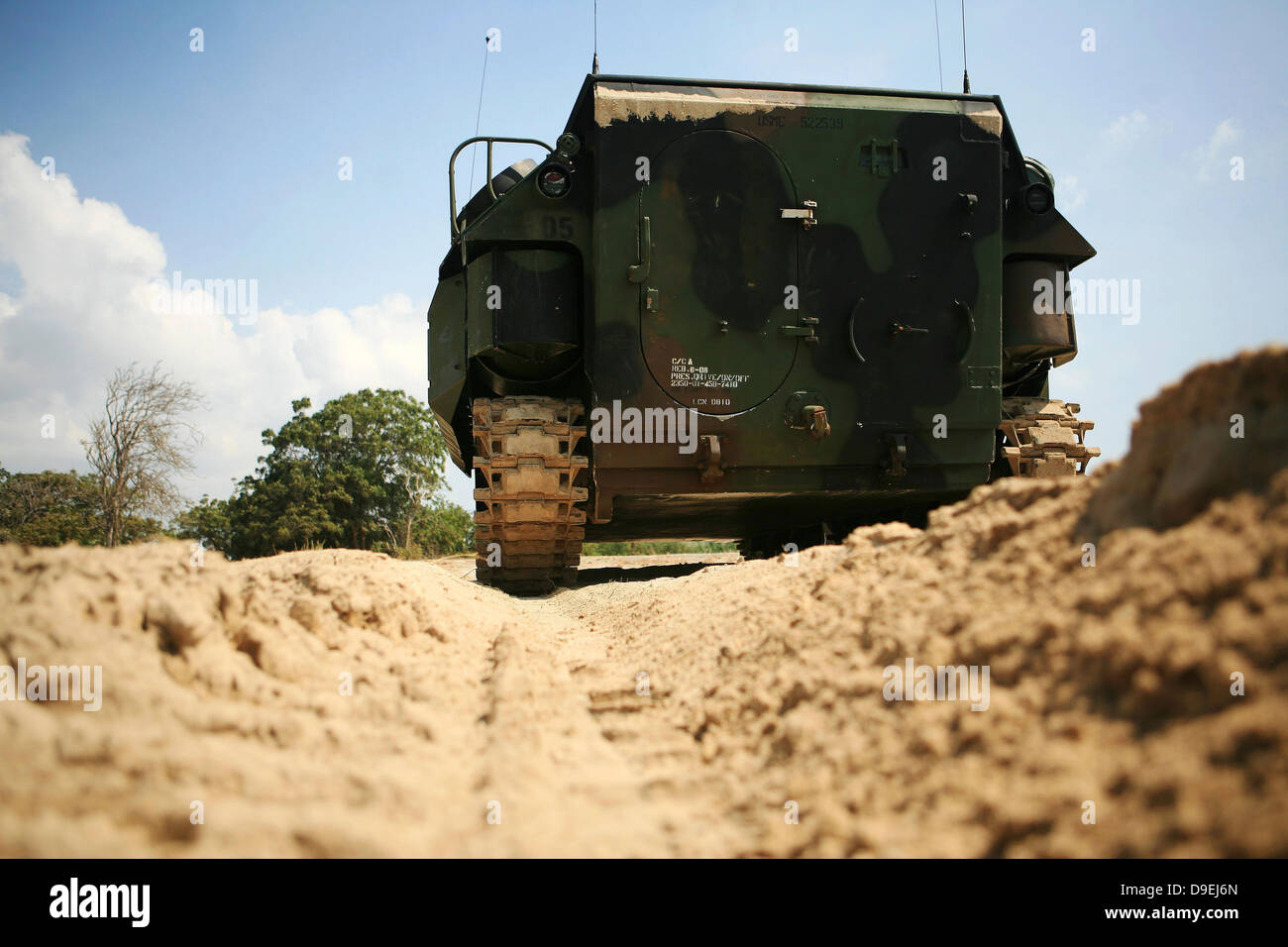 Low angle rear view of an amphibious assault vehicle driving along the beach. - Stock Image