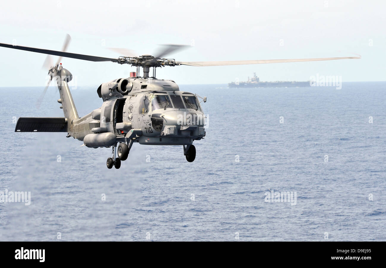An MH-60R Seahawk helicopter in flight over the Pacific Ocean - Stock Image