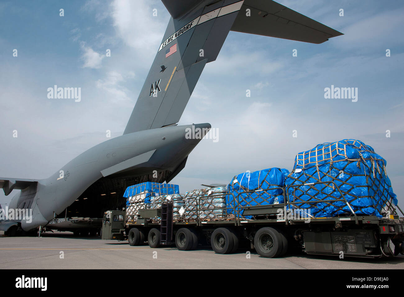A Japanese soldier marshals vehicles from a C-17 Globemaster III. - Stock Image
