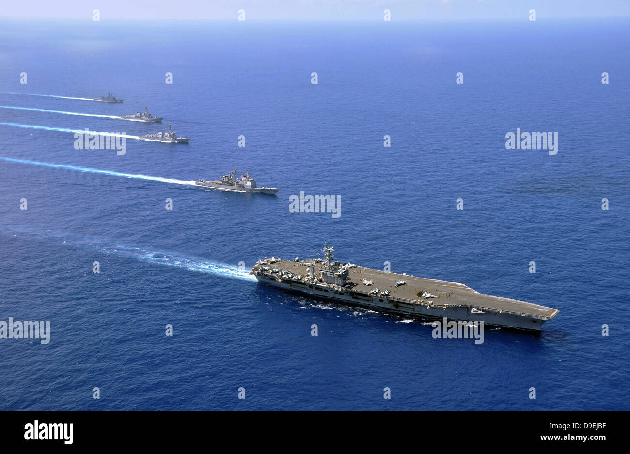 Military ships operate in formation in the South China Sea. - Stock Image