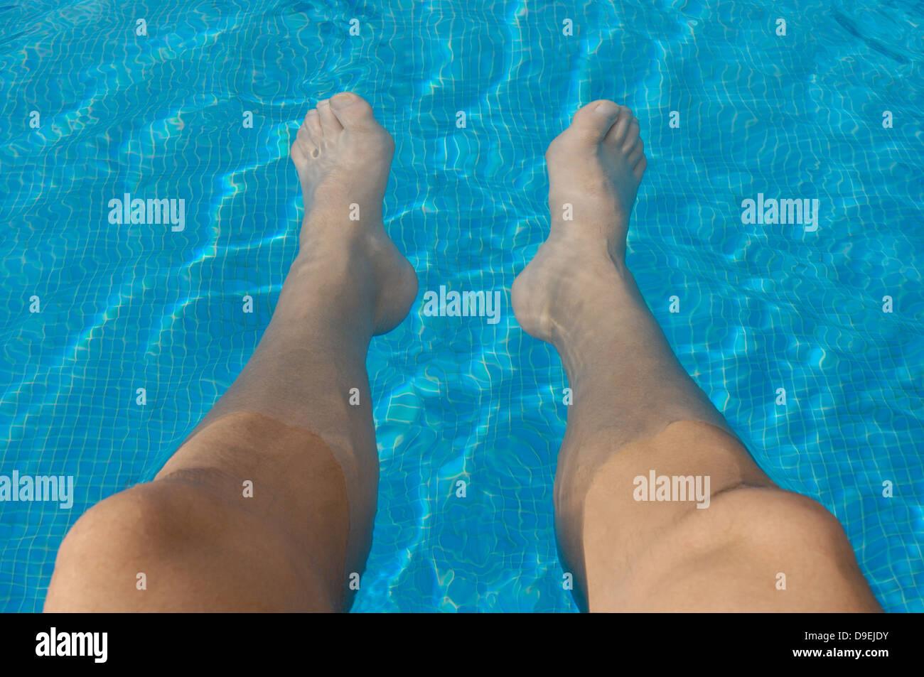 Man's legs dangle in the swimming pool - Stock Image