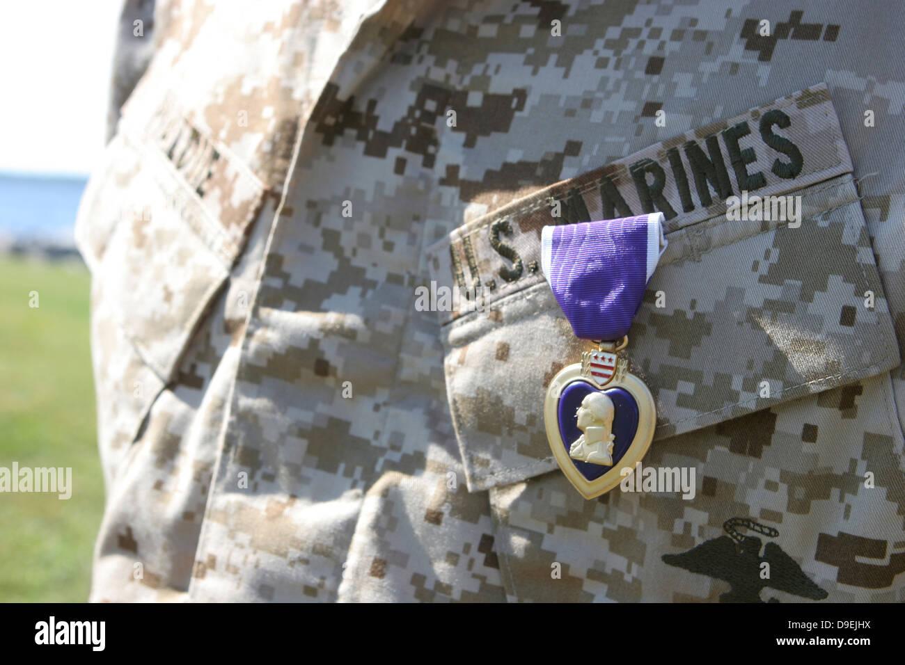 The Purple Heart award hangs over the heart of a U.S. Marine. - Stock Image