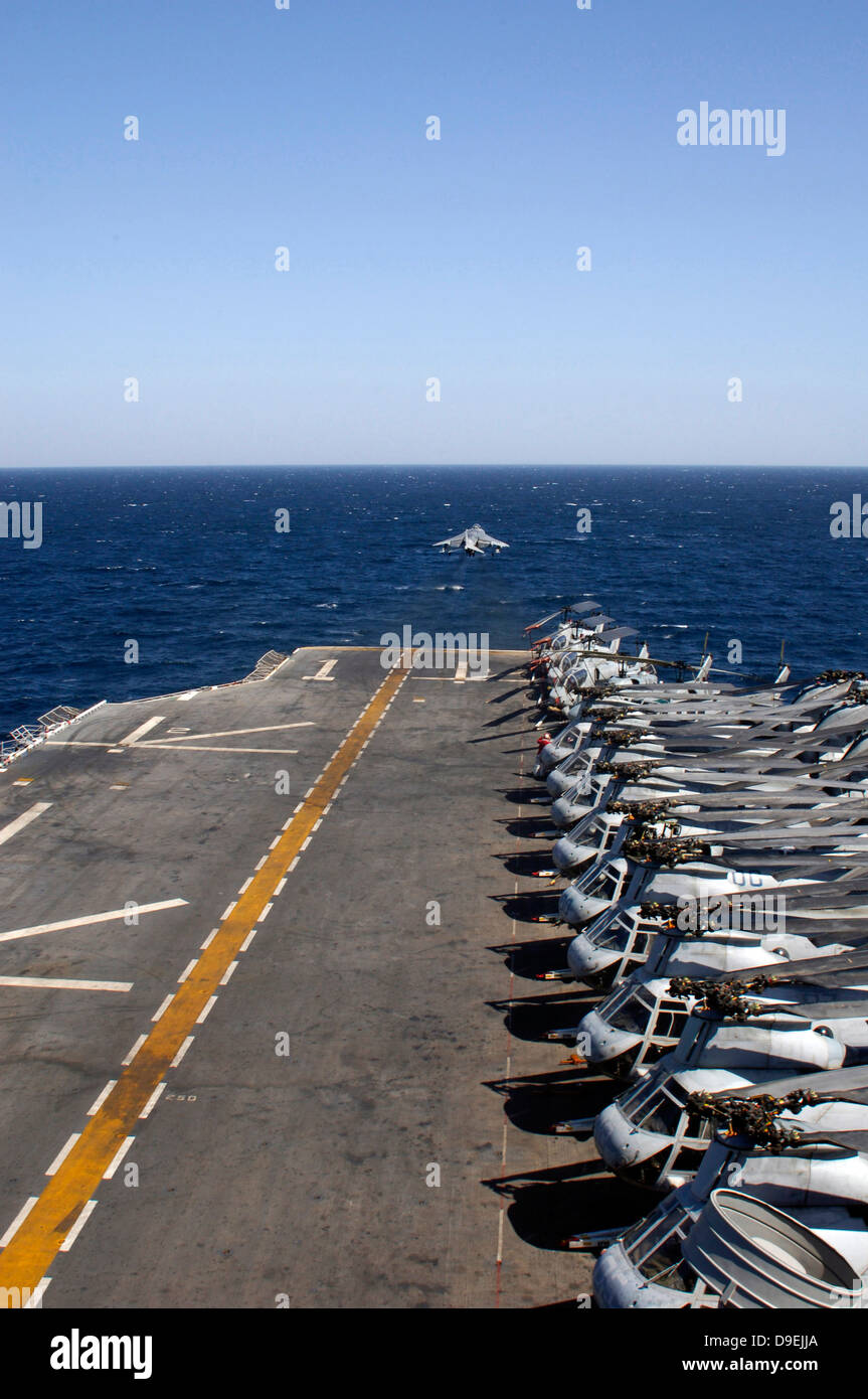 An AV-8B takes off from the flight deck of USS Tarawa lined with helicopters. - Stock Image