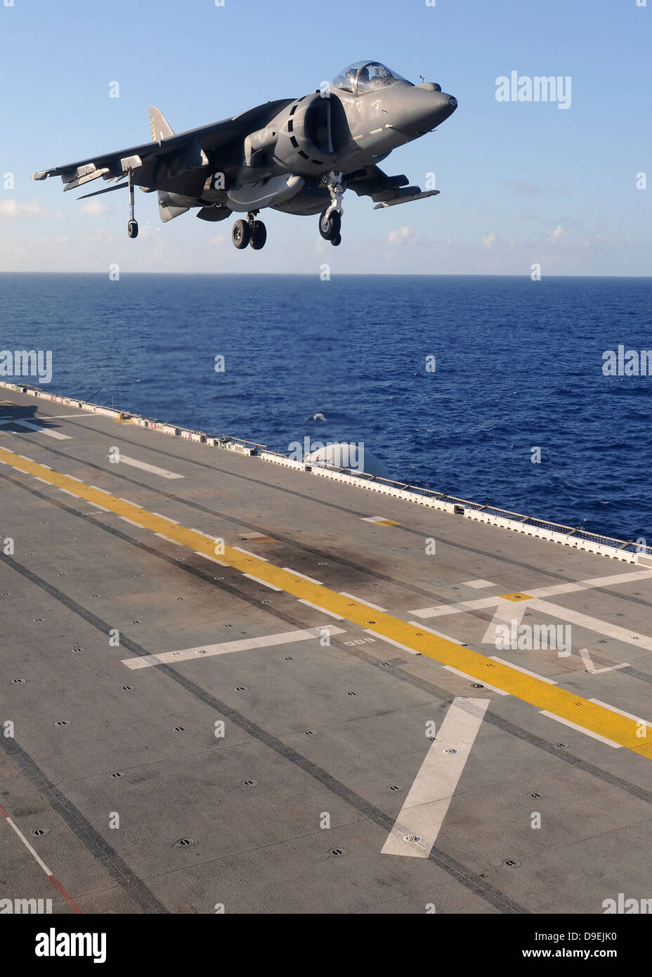 An AV-8B Harrier jet prepares to land on the flight deck of USS Essex. Stock Photo