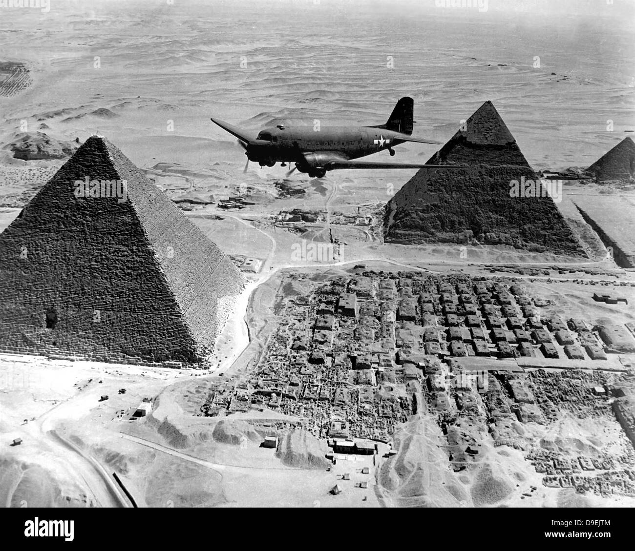 An Air Transport Command plane flies over the pyramids in Egypt. Stock Photo