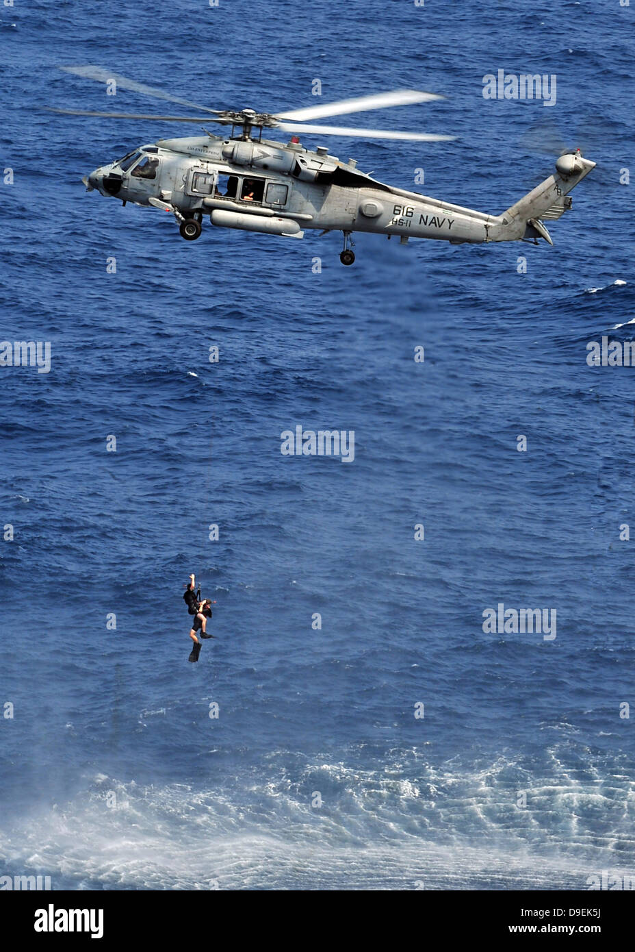 Search and rescue swimmers being hoisted into a helicopter. - Stock Image